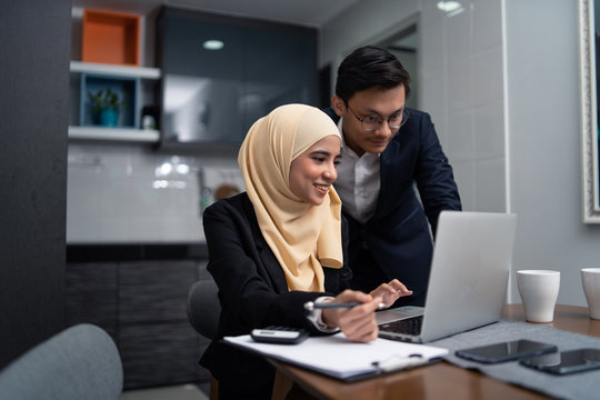asian malay couple working together at home with laptop and calculator