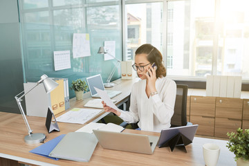 Pretty Vietnamese female business executive working in modern office
