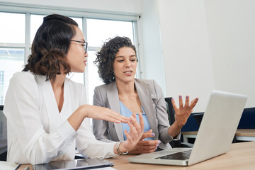 Female coworkers arguing about information on laptop screen