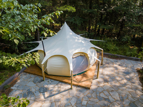 Aerial drone shot of a glamping tent in a forest