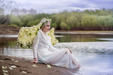 Nice blonde girl with white flower wings near river