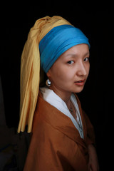 """Makeup artist He Yuhong poses for a photo after removing her makeup that transformed her into the """"Girl with a Pearl Earring"""" at her house in Chongqing"""