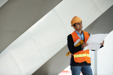 Portrait of engineer with blueprint inspecting construction site