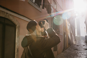A street photographer or a young man takes pictures of authentic houses in Lisbon in Portugal. A professional photographer or tourist taking pictures for memory.