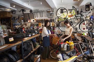 女性店員が自転車にカゴを取り付けようとしている
