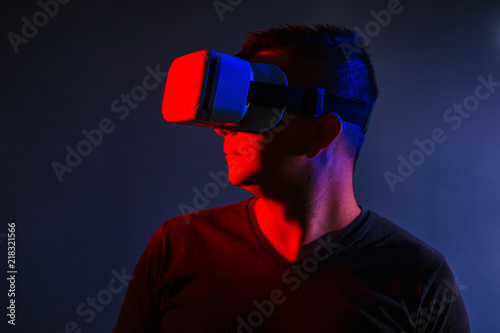 62de9b737276 The man with glasses of virtual reality on black isolated background. Young  guy in VR headset is looking right. Playing mobile game app on device
