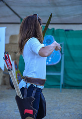 female professional archer shooting position