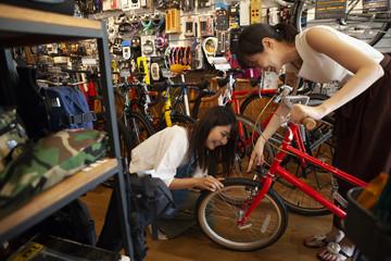 自転車のタイヤの空気が入っているか確認するスタッフ