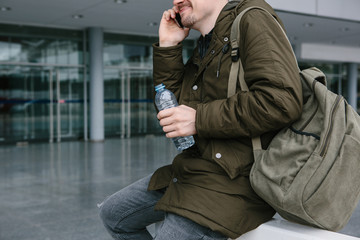 A young male tourist at the airport or near a shopping center or station calls a taxi or talks on a cell phone or communicates with friends using a mobile phone.