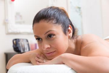 Frau liegt auf Liege im Massagesalon