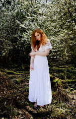 Beautiful model with long red hair dressed in white against blossom trees