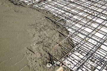 pouring concrete into prepared place with reinforced metal frame