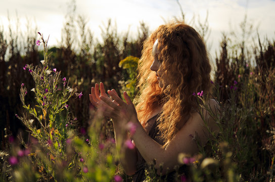 Woman with beautiful cascading long red hair standing amongst wild flowers highlighted by the sun