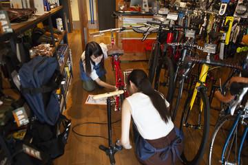 自転車の空気の入れ方を確認する女性とスタッフ