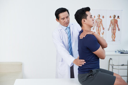 Mature osteopath palpating low back of patient in his office
