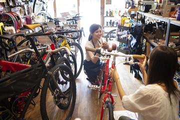 お店で自転車について話している女性とスタッフ