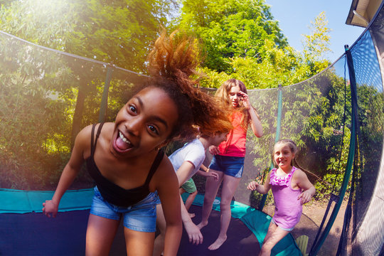 African girl playing with friends on trampoline