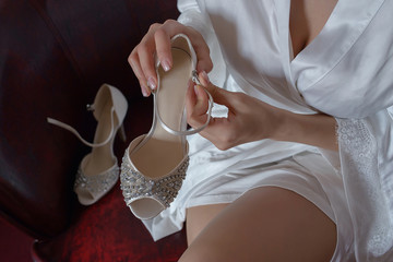 Cropped shot of Caucasian young woman wearing a silky bridal kimono robe or gown, holding an embellished silk sandal in her hand and fixing the clasp, the bride's morning preparation