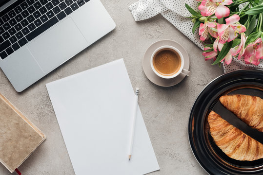 top view of cup of coffee with blank paper, croissants and laptop on concrete surface