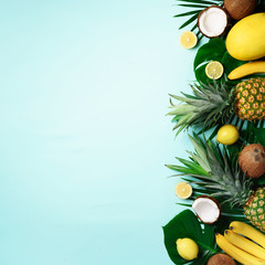 Fototapeta Exotic pineapples, ripe coconuts, banana, melon, lemon, tropical palm and monstera leaves on blue background with copyspace for text. Square crop. Creative layout. Summer concept. Flat lay, top view