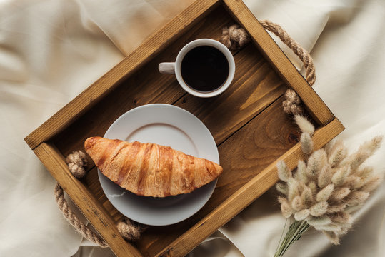 top view of coffee and croissant on tray with lagurus ovatus bouquet on beige cloth, breakfast in bed concept