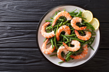 Organic food, salad: shrimps with green beans, cheese and lemon close-up on a plate. horizontal top view from above