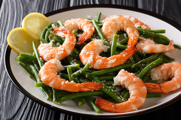 King prawns with green beans, cheese and lemon close-up on a plate. horizontal