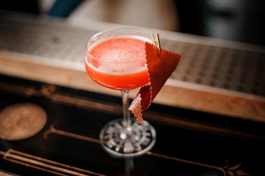 Tasty sweet alcoholic orange cocktail with foam