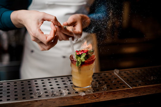 Barman making tropical summer cocktail decorated with flowers