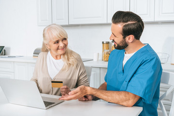 smiling young caregiver looking at senior woman holding credit card and using laptop