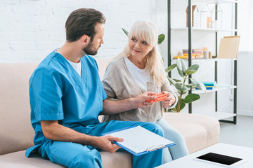 young male nurse holding clipboard and giving glass of water with pills to senior woman
