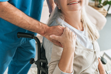 cropped shot of smiling senior woman in wheelchair holding hand of caregiver