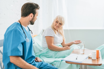 doctor with stethoscope looking at senior woman taking medicine in hospital bed