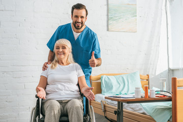 happy senior woman in wheelchair smiling at camera and cheerful young doctor showing thumb up