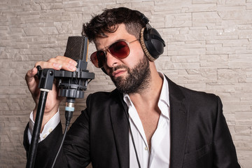 Singer with sunglasses in front of a microphone holding him by hand and with some helmets