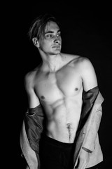 Portrait of fashion young caucasian sexy muscled attractive handsome athletic man boy model isolated on black background