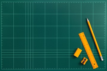 Flat lay picture of orange stationery on top the green cutting mat