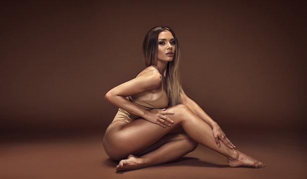 Sensual brunette woman with ideal tan body.