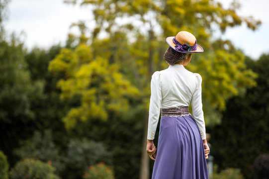 Beautiful girl in a vintage dress. Girl on a blurred background. A girl in a white blouse and a purple dress. A woman is dressed in retro style. The girl is straightening the hat on her head.