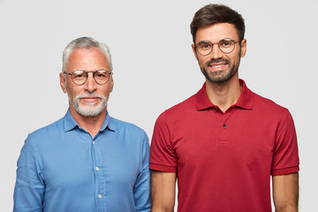 Mature grey haired man and his adult son stand against white background, have pleased expressions after meeting, wear round spectacles, being one friendly family. People and generation concept