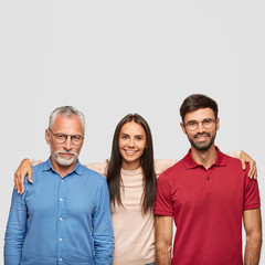 Happy family pose for making common photo: positive senior father, adult daughter and son embrace each other, smile friendly, pose against white background. People, generation and relations concept