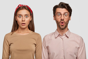 Wall Mural - Attractive young couple with shocked expressions hear some noise downstairs, thinks it could be robber, stare with frightened looks stand next to each other against white studio wall. Emotions concept