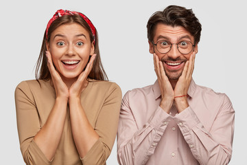 Wall Mural - Amazed beautiful young European female and handsome bearded guy keep hands under chin, smile positively, see something pleasant in front, have happy expressions, isolated over white background