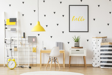 Small wooden desk and a modern chair for a young pupil and creative, vibrant yellow decorations in a scandinavian style child bedroom interior with white walls Wall mural