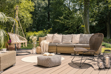 Pouf and rattan chair on wooden patio with settee in the garden during summer. Real photo