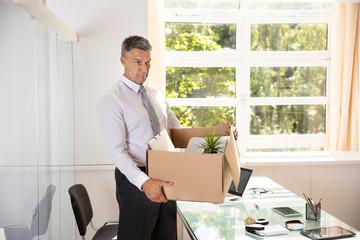 Unhappy Businessman Carrying Belongings In Cardboard Box