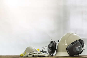 PPE onsist with White safety helmet (hard hat) with ear muff attached,Respiratory protection, Pair of leather gloves and transparent plastic glasses, Engineering and construction concept. Wall mural