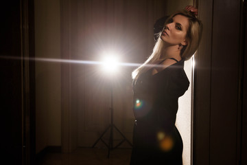 portrait of a girl in a black dress posing in the backlight