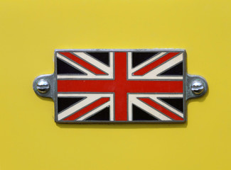 VA Vintage British Union Jack flag badge on a yellow car close up