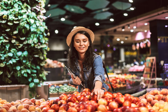 Beautiful smiling girl in hat happily choosing peaches in supermarket